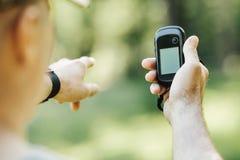 供以人员举行一台GPS接收器和计划在他的手上 库存图片