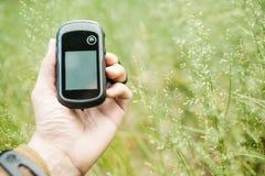 供以人员举行一台GPS接收器和计划在他的手上 图库摄影