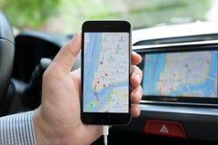 供以人员举行与苹果计算机地图和汽车戏剧的iPhone 6 免版税图库摄影