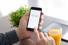 供以人员举行与谷歌的iPhone 6在屏幕上 免版税库存图片