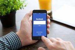 供以人员举行与Facebook的iPhone 6在屏幕上 库存照片