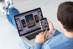 供以人员举行与IOS的手iPhone在屏幕和MacBook 库存照片