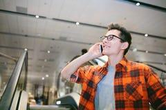 供以人员举行在商城背景的智能手机 免版税库存照片