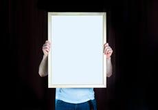 供以人员举行木框架,嘲笑,在黑背景 库存图片