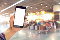 供以人员举行,并且使用智能手机在登记终端机场背景 图库摄影