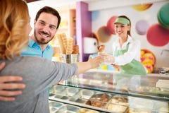供以人员买的冰淇凌给女孩在酥皮点心商店 图库摄影