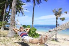 供以人员休息在吊床在海滩的棕榈树下与白色沙子和天蓝色海 库存图片