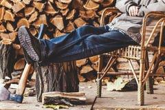 供以人员休息在椅子并且把他的脚放在树桩上 免版税库存照片