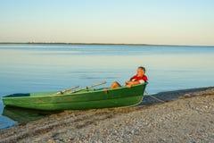 供以人员休息在海滩的一条小船 免版税库存照片