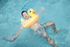 供以人员佩带一支黄色鸭子可膨胀的管和使用在水池 免版税库存照片