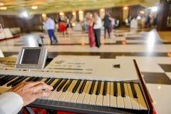 供以人员使用在一架电子钢琴的谁在餐馆 库存图片