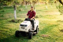 供以人员使用在割草机,男性骑马草坪拖拉机和放松的工作者乘驾在日落金黄小时 库存图片