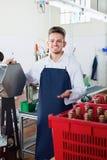 供以人员使用机器的工作者在工厂装瓶酒 免版税库存图片