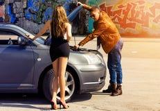 供以人员修理性感的亭亭玉立的白肤金发的女孩的一辆汽车 图库摄影