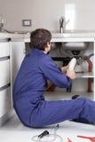 供以人员修理管子坐地板 库存图片