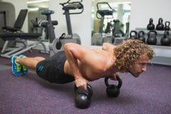 供以人员做与水壶响铃的俯卧撑在健身房 库存图片