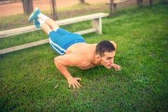 供以人员做俯卧撑在公园、体型和训练 与户外赤裸上身的人的健身概念,做行使 免版税图库摄影