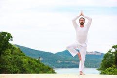 供以人员做印地安经典瑜伽在海和山 免版税库存照片