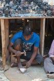 供以人员做和卖菩萨雕象在市场 库存照片