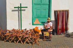 供以人员做坐与凳子和传送带的皮革物品待售在老大厦前面 免版税库存图片