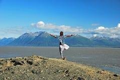 供以人员做瑜伽在面对山的海岸线在Turnagain胳膊 免版税图库摄影