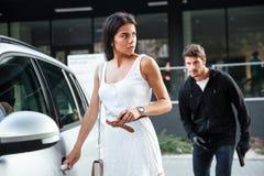 供以人员偷偷靠近对少妇的强盗打开她的汽车 免版税库存图片