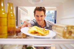 供以人员充分看起来里面冰箱不健康的Foodï ¿ ½ 免版税库存图片