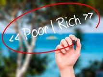 供以人员写贫寒-有黑标志的富有的手在视觉屏幕上 免版税库存照片