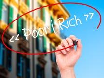 供以人员写贫寒-有黑标志的富有的手在视觉屏幕上 库存照片