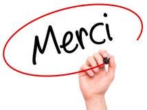 供以人员写Merci (谢谢用法语)与黑标志的手 免版税库存照片