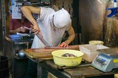 供以人员切开鱼在东京鱼市上 免版税库存照片