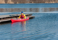 供以人员划皮船在河01的红色皮船 库存照片