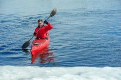 供以人员划皮船在河02的红色皮船 免版税库存照片