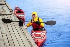 供以人员划皮船在河13的红色皮船 库存图片