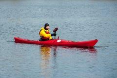 供以人员划皮船在河16的红色皮船 免版税库存图片