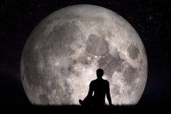 供以人员单独坐草和看在月亮 想象未来概念 免版税库存图片
