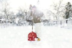 供以人员取消在后院的雪与铁锹在降雪期间 免版税库存照片