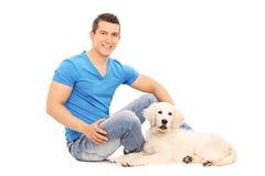 供以人员变冷与在地板上供以座位的他的小狗 免版税库存照片