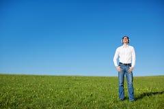 供以人员听到在一个晴朗的绿色领域的音乐 免版税库存照片