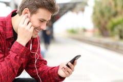 供以人员听到等待在火车站的音乐 免版税库存照片