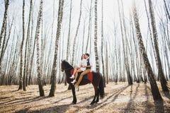供以人员和一起骑棕色马的妇女 免版税库存照片