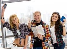 供以人员和两持与票和地图的妇女一本护照 观看照相机并且显示赞许 微笑 愉快 库存图片