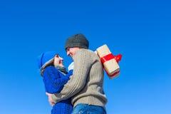 供以人员和在色的房子背景的女孩拥抱有礼物的 库存照片