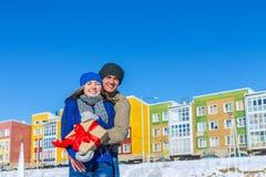 供以人员和在色的房子背景的女孩拥抱有礼物的 库存图片