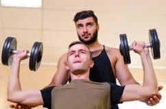 供以人员和他的行使与哑铃的个人教练员在健身房 肩膀的技术锻炼 有coac的新手运动员 免版税库存图片
