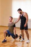 供以人员和他的行使与哑铃的个人教练员在健身房 免版税图库摄影