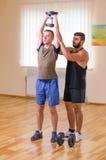 供以人员和他的行使与哑铃的个人教练员在健身房 图库摄影