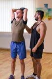 供以人员和他的行使与哑铃的个人教练员在健身房 免版税库存图片