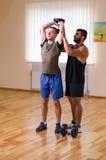 供以人员和他的行使与哑铃的个人教练员在健身房 库存图片