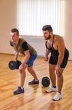 供以人员和他的行使与哑铃的个人教练员在健身房 库存照片